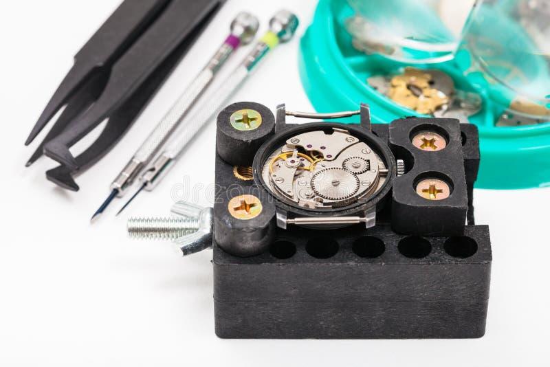 Właściciel z zegarkiem i narzędziami dla naprawiać zegarek zdjęcia stock