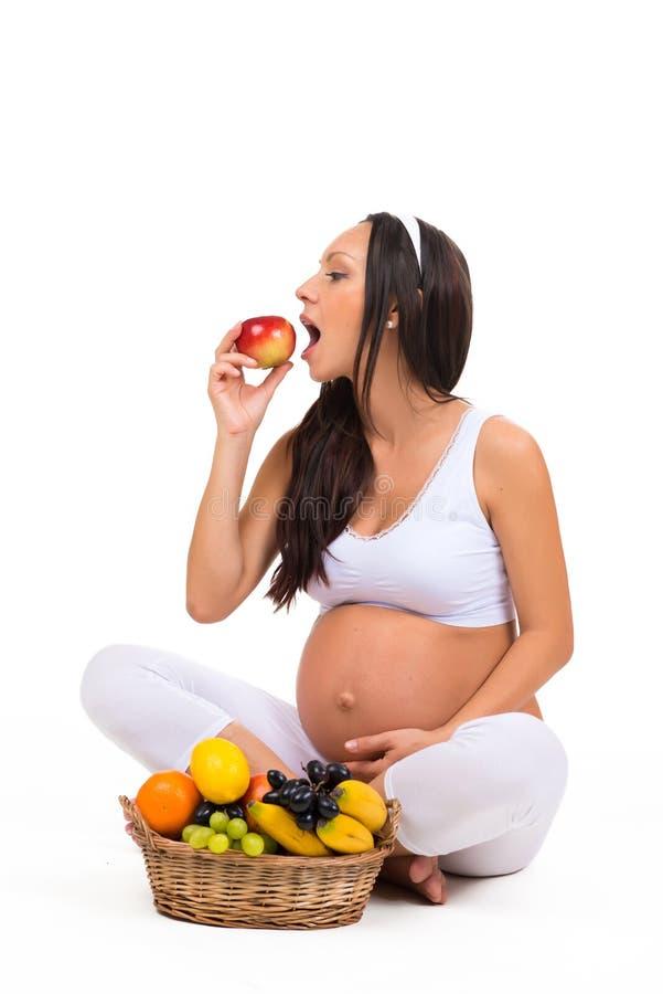 Właściwy odżywianie podczas brzemienności Witaminy i owoc Kobieta w ciąży je jabłka zdjęcia stock
