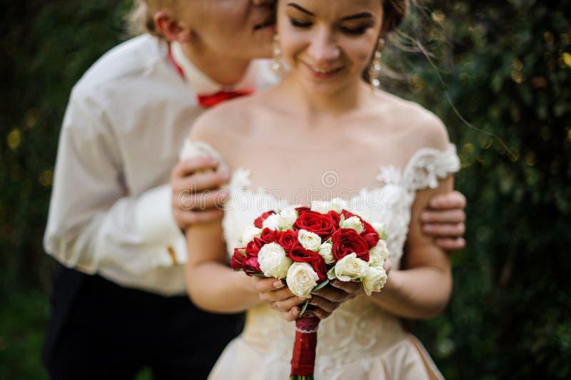 Właśnie żonatego mężczyzny całowania panna młoda w zielonym parku obraz stock