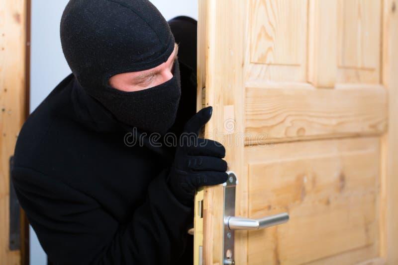 Włamania przestępstwo - włamywacz otwiera drzwi zdjęcie royalty free