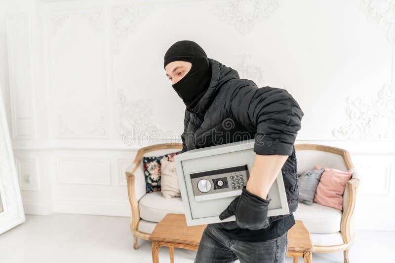 Włamywacz popełnia przestępstwo w Luksusowym mieszkaniu z stiukiem Złodziej kraść nowożytną Elektroniczną skrytkę z czarnym balac fotografia stock