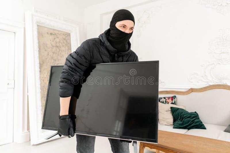 Włamywacz popełnia przestępstwo w Luksusowym mieszkaniu z stiukiem Złodziej kraść nowożytny drogiego z czarnym balaclava zdjęcie stock