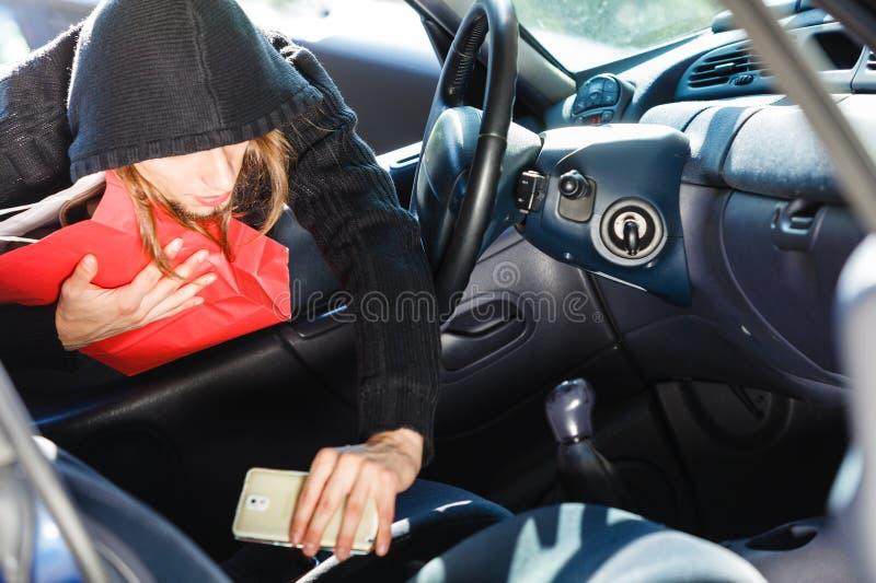 Włamywacza złodziej kraść smartphone i torbę od samochodu obrazy stock