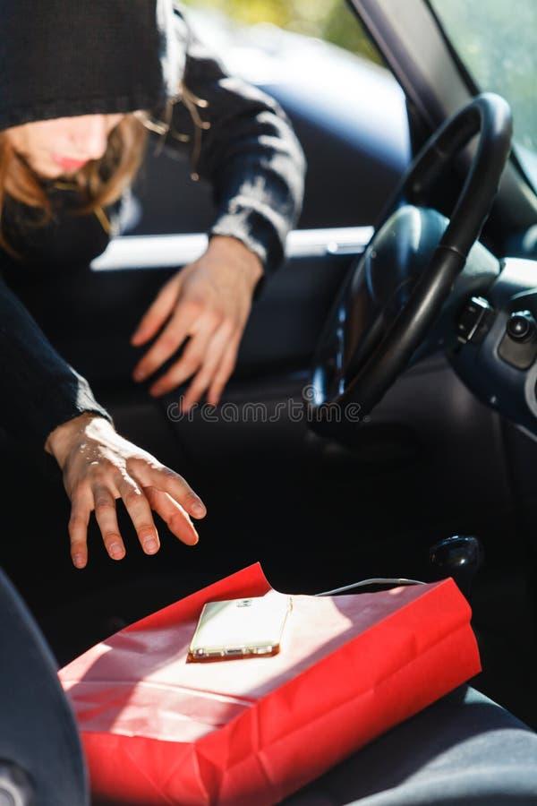 Włamywacza złodziej kraść smartphone i torbę od samochodu obrazy royalty free