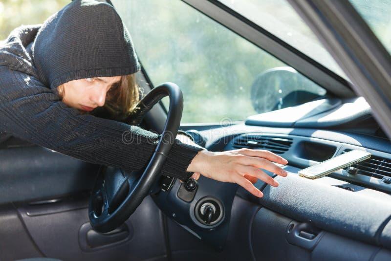 Włamywacza złodzieja łamanie w samochodowego kraść smartphone obrazy royalty free