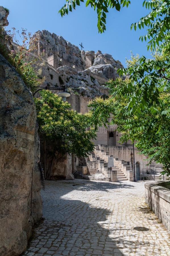 Włochy Matera Sasso Caveoso Stara brukowana ulica Glimpse z skalistym wzgórzem o nazwie Monterone obraz stock