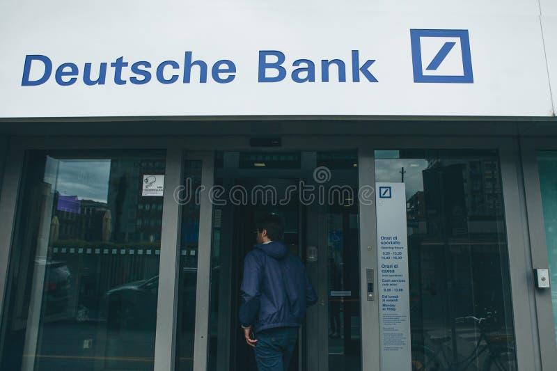 Włochy, Mediolan, 30 maja 2019 r.: Mężczyzna wchodzi do drzwi niemieckiego banku Deutsche Bank Instytucja finansowa zdjęcie royalty free