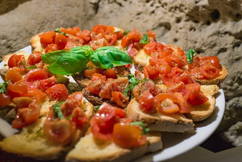 Włoscy bruschettas z siekającym pomidorem i basilem przygotowywającymi dla brea obrazy stock