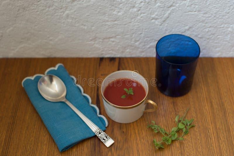Włoscy pomidorowi zupni oregano liście słuzyć w Chińskich porcelan naczyniach w bielu i złota kolorach z srebną łyżką zdjęcia stock