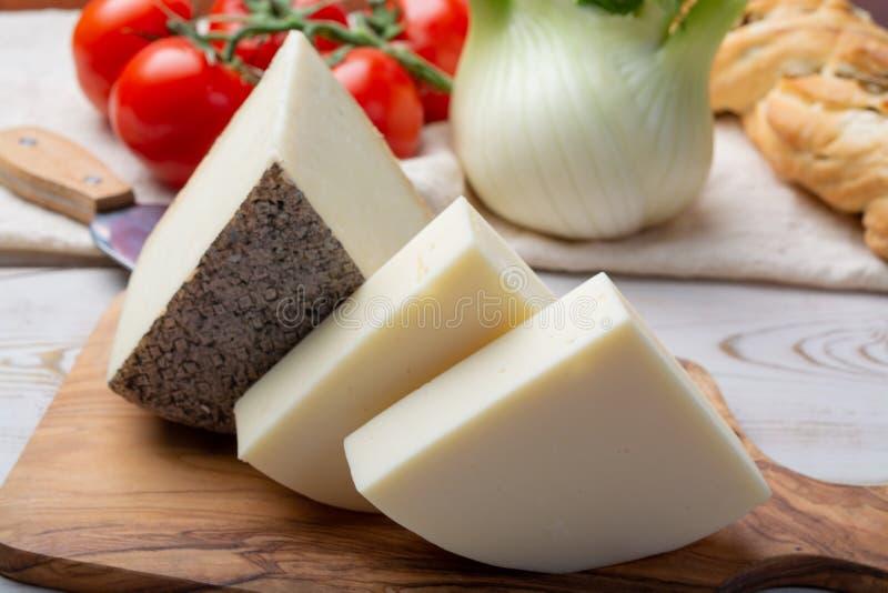 Włoscy sery, dojrzałej toskanki Pecorino barani ser i Provolone dolce krowy ser, słuzyć z oliwnym chlebem i pomidorami obrazy stock