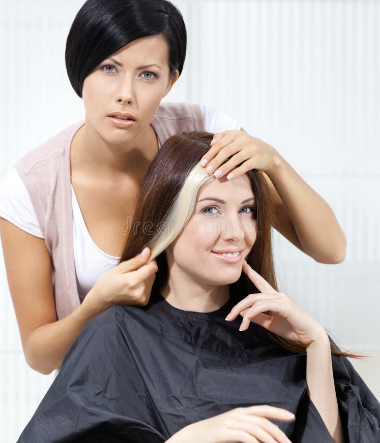 Włosianego stylisty prób kędziorek farbujący włosy na kliencie zdjęcie royalty free