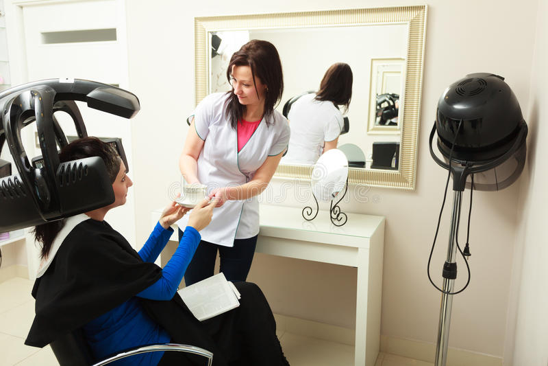 Włosiany salon. Fryzjer daje filiżanki kobiety kawowego klienta. Nowożytny wyposażenie. obraz royalty free