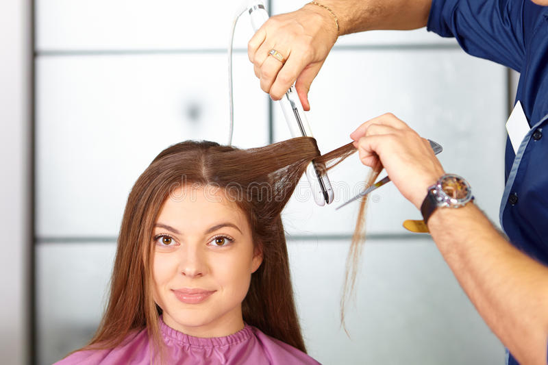 Włosiany salon Kobiety ostrzyżenie Use prostownica zdjęcie stock