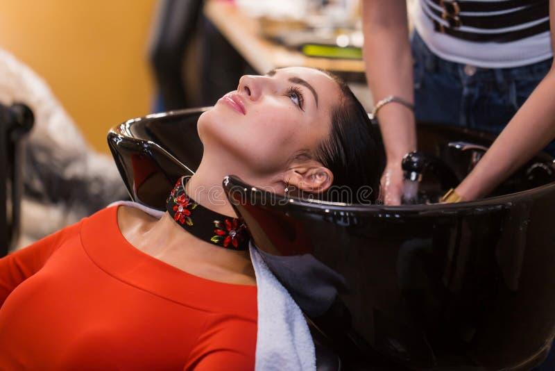 Włosiany stylista, fryzjera płuczkowy włosy klient przed robić fryzurze obrazy stock