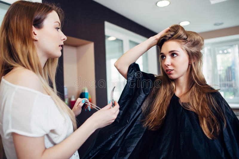 Włosiany stylista pracuje na żeńskim klienta s uczesania ścinku splata z włosianymi szpilkami w fryzjerstwa studiu obrazy royalty free