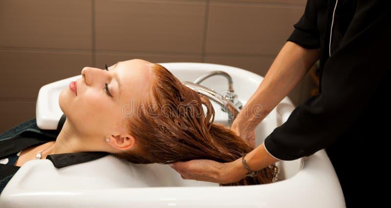 Włosiany stylista przy pracą - fryzjera płuczkowy włosy klient obrazy stock