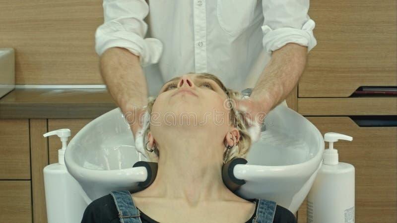 Włosiany stylista przy pracą - fryzjera płuczkowy włosy klient przed robić fryzurze zdjęcie royalty free