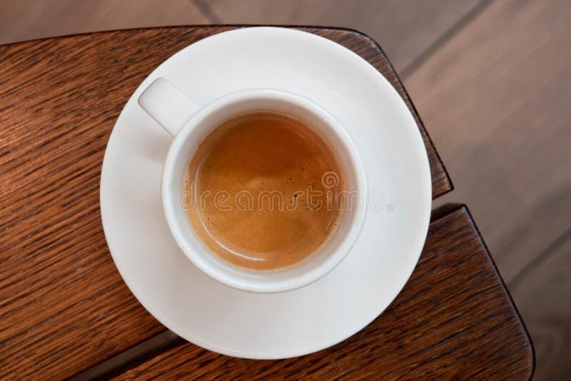 Włoska kawa espresso w białej ceramicznej filiżance z spodeczkiem na brązu drewna stole z góry Brurred tło zdjęcia stock