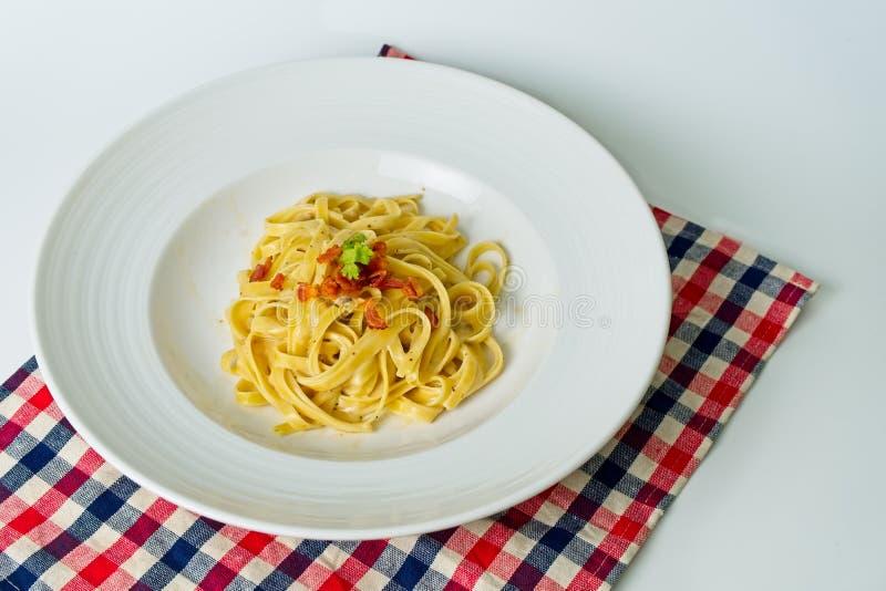Włoska kuchnia, Fettuccine Carbonara z bekonem umieszczającym na białym naczyniu z białym tłem obraz stock