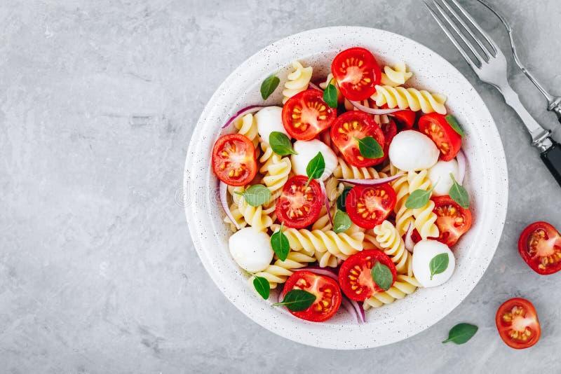 Włoska makaron sałatka z pomidorami, mozzarella serem, czerwoną cebulą i basilem, Odg?rny widok fotografia stock