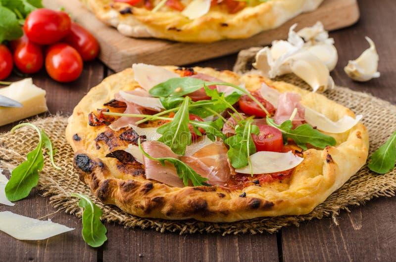 Włoska pizza z parmesan serem, prosciutto i arugula, fotografia stock