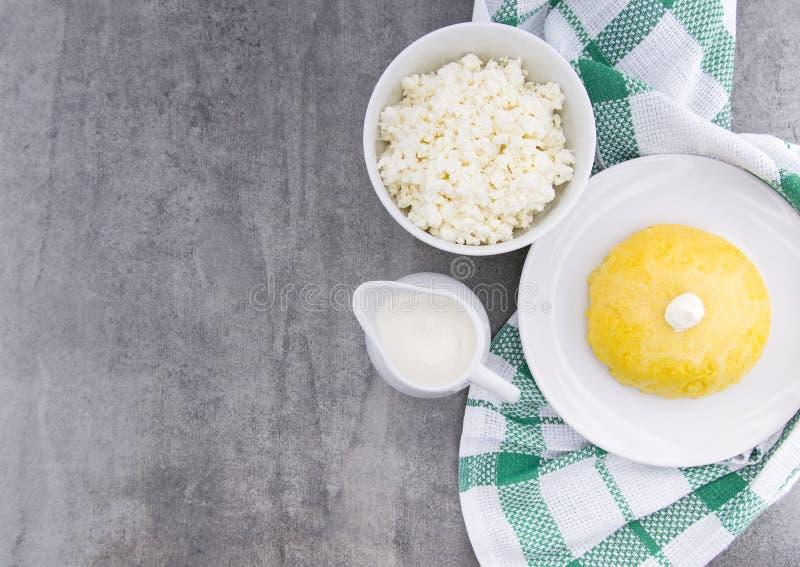 Włoska tradycyjna polenta, owsianka robić od cornmeal Mamaliga Z chałupa serem i kwaśną śmietanką na nieociosanym tle zdjęcie royalty free