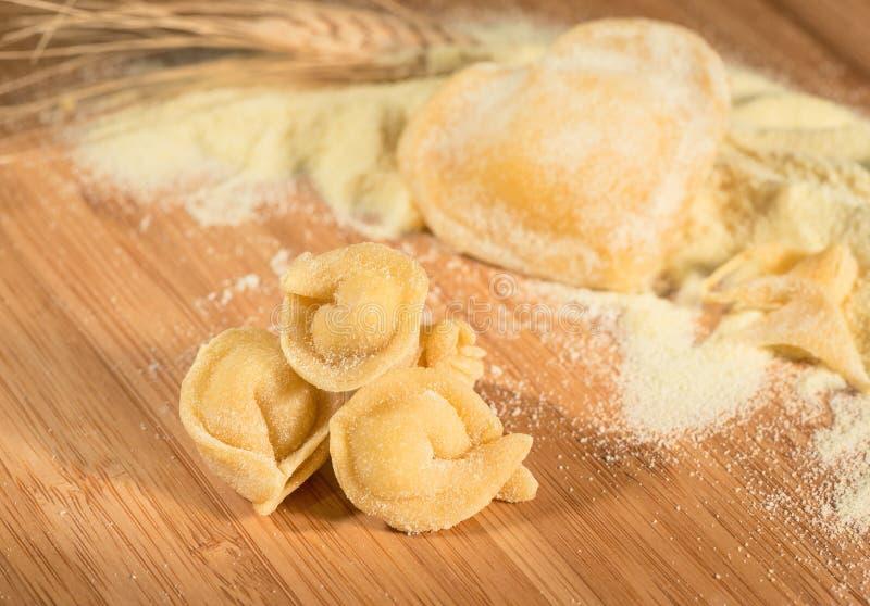 Włoski domowej roboty tortellini z mąką, surowym ciastem, ucho pszeniczny i kierowym kształtnym pierożkiem, zdjęcie stock