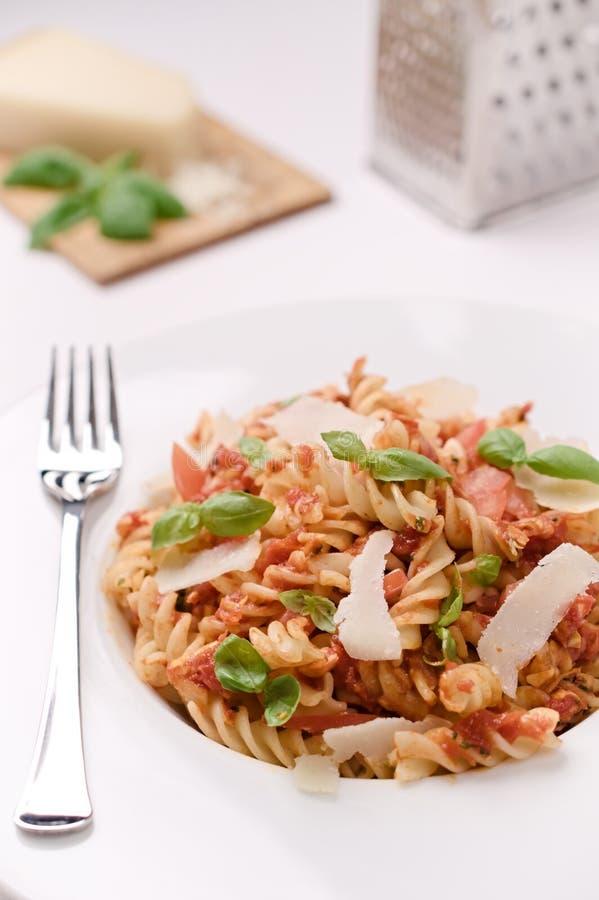 Włoski fusilli makaron z pomidorowego kumberlandu, basilu i parmesan chee, zdjęcie stock