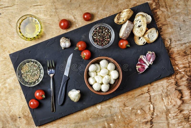 Włoski jedzenie, bruschettas, serowi mozzarella składniki, pikantność, kucharstwo, basil, czosnek czarna deska, wieśniaka styl, c zdjęcia royalty free