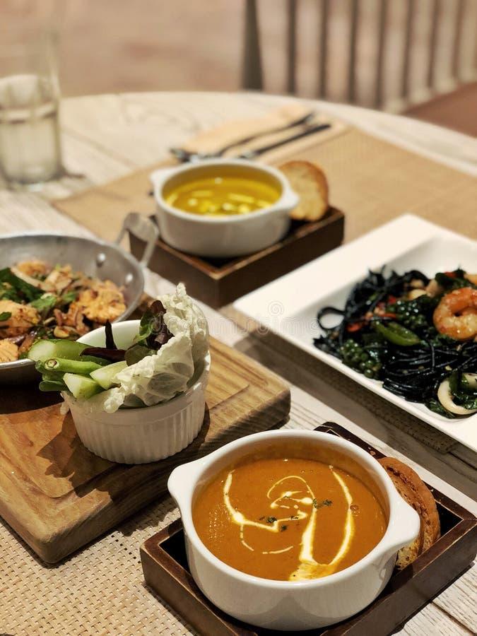 włoski jedzenie homara bisque polewka, dyniowa polewka, atramentu makaron i łososiowa sałatka, obrazy stock