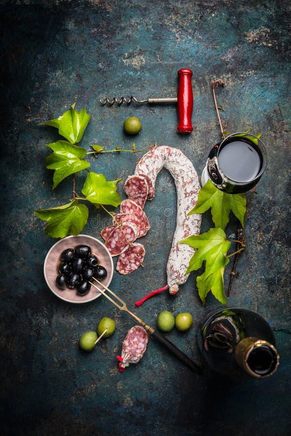 Włoski karmowy styl życia z salami, czerwonym winem, winogrono liśćmi i oliwkami na ciemnym tle, odgórny widok obrazy royalty free