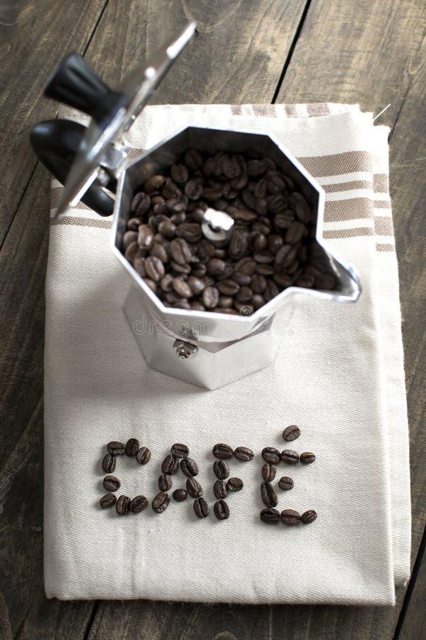 Włoski kawowego producenta garnek wypełniał z kawowymi fasolami zdjęcia royalty free