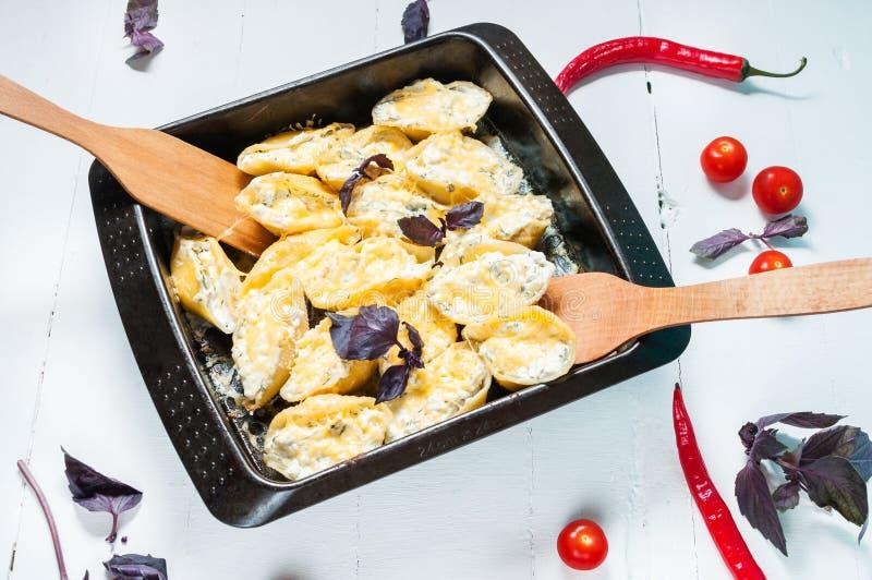 Włoski makaron Conchiglioni Rigati faszerował z serem na białym drewno stole zdjęcia royalty free