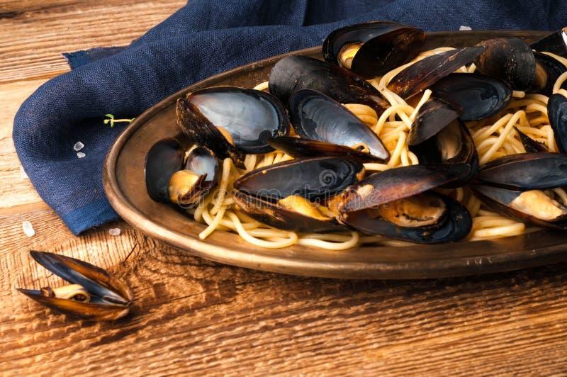 Włoski makaron z mussels na metalu talerzu blisko błękitnej pieluchy obrazy stock