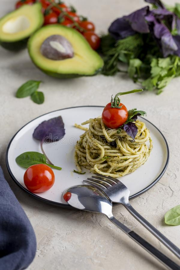 Włoski makaron z pesto, ziele i czereśniowymi pomidorami przy bielu talerzem, zdjęcia royalty free