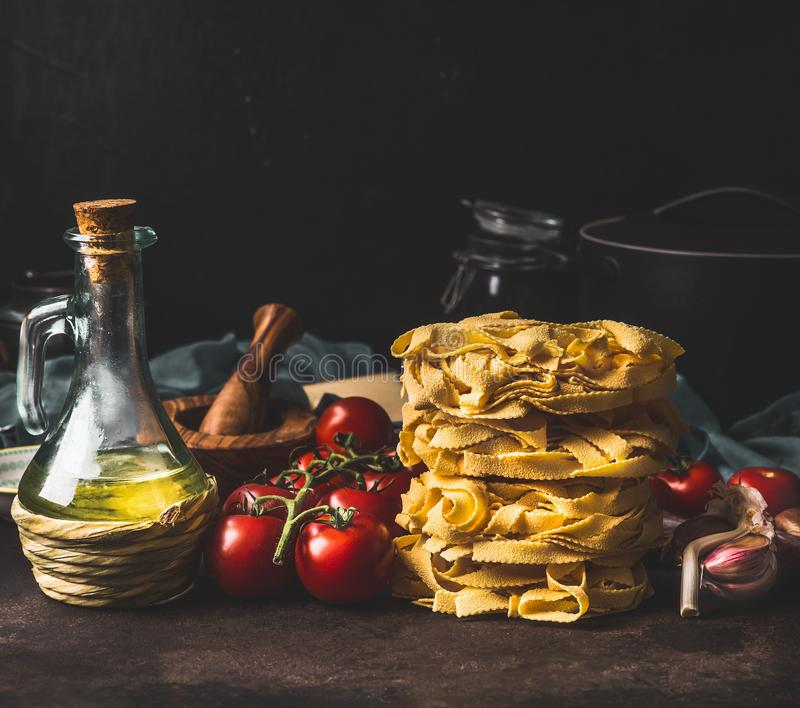 Włoski makaron z pomidorami, oliwka olejem i czosnkiem na ciemnym nieociosanym kuchennym kontuarze przy ciemnym tłem, carpaccio k obraz stock