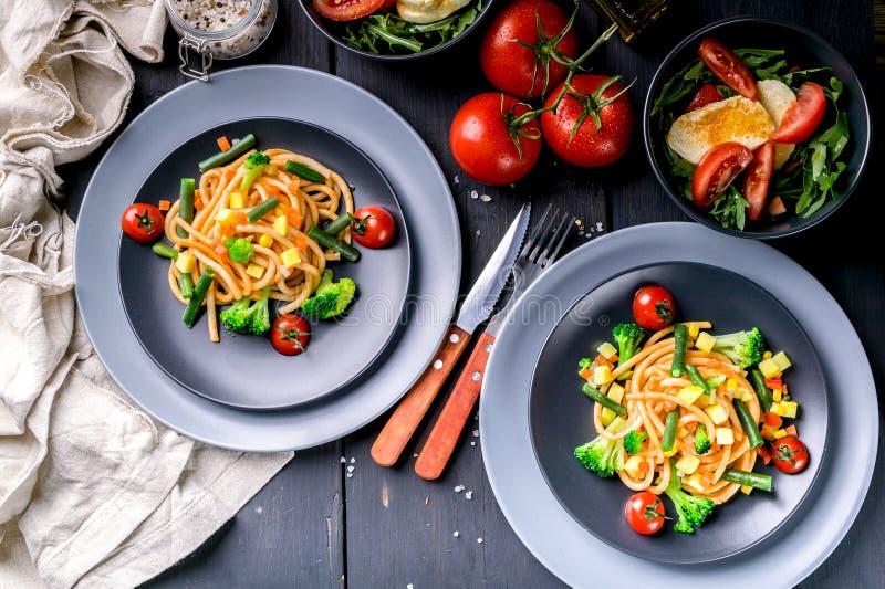 Włoski makaron z warzywami i sałatką z arugula i mozzarellą na ciemnym drewnianym tle Tradycyjna ?r?dziemnomorska kuchnia fotografia royalty free