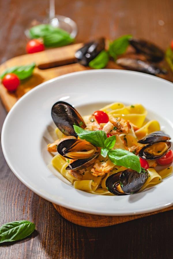 Włoski makaronu pappardelle z mussels i łososiem na bielu talerzu obraz stock