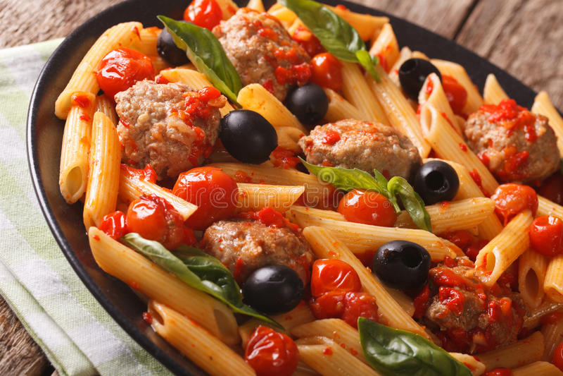 Włoski makaronu penne z klopsikami, oliwkami i pomidorowego kumberlandu clos, obraz royalty free