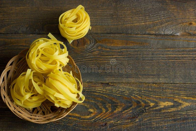 Włoski makaronu tagliatelle w koszu na stole fotografia royalty free