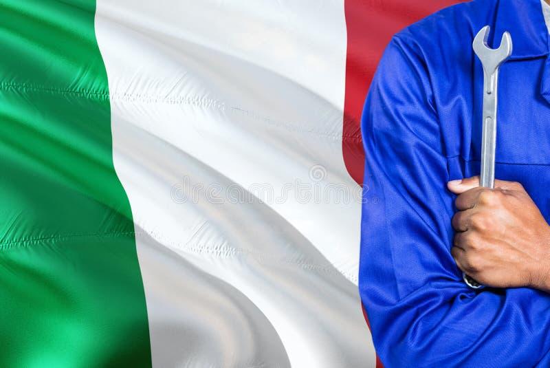 Włoski mechanik w błękita mundurze trzyma wyrwanie przeciw machać Włochy chorągwianego tło Krzyżujący ręka technik obrazy stock