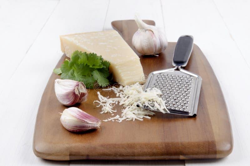 Włoski parmesan ser z czosnkiem, świeżymi kolenderami i grater, zdjęcie royalty free