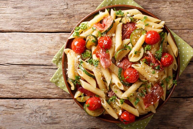 Włoski penne makaron z prosciutto, pomidorem, zucchini i pa baleronu, zdjęcia stock
