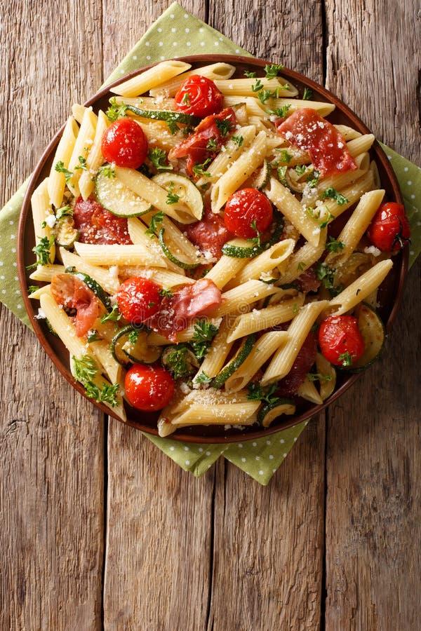 Włoski penne makaron z prosciutto, pomidorem, zucchini i pa baleronu, obraz royalty free