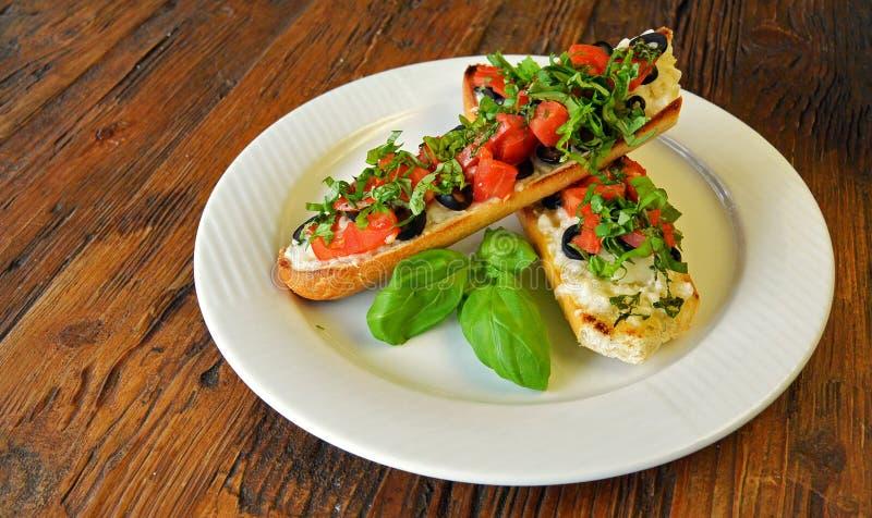 Włoski pomidorowy bruschetta z oliwkami na drewnianym zdjęcia stock