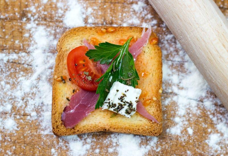 Włoski pomidorowy bruschetta z pomidorem, ziele, pancetta i olejem na chlebie siekającymi, piec na grillu lub wznoszącym toast dr obrazy royalty free