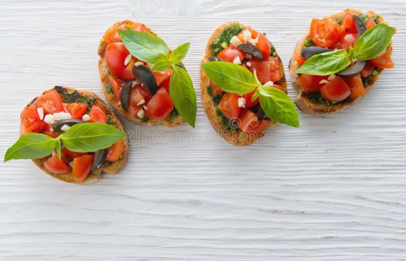 Włoski pomidorowy bruschetta z warzywami, ziele i olejem siekającymi, zdjęcia royalty free