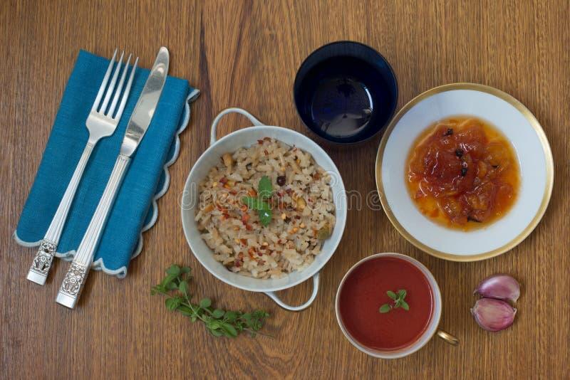Włoski pomidorowy zupny Brown ryż risotto melonowa deser słuzyć w Chińskich porcelan naczyniach w bielu i złota kolorach z srebny zdjęcie royalty free