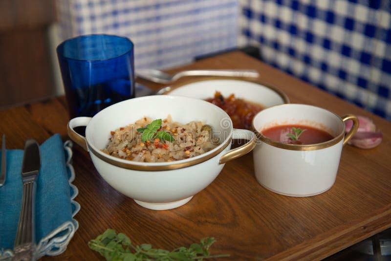 Włoski pomidorowy zupny Brown ryż risotto melonowa deser słuzyć w Chińskich porcelan naczyniach w bielu i złota kolorach z srebny obrazy royalty free