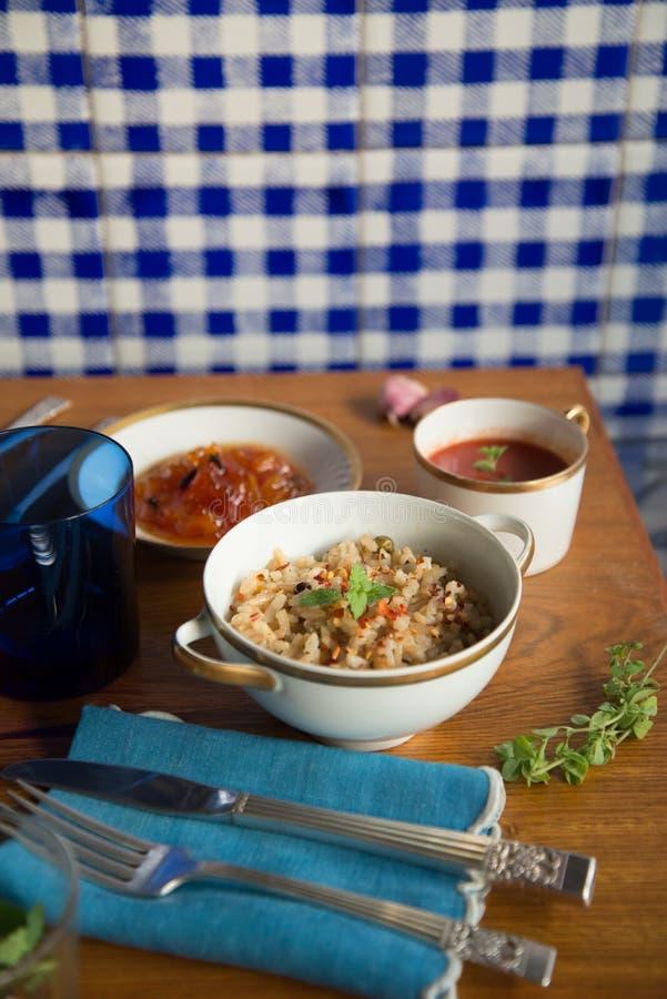 Włoski pomidorowy zupny Brown ryż risotto melonowa deser słuzyć w Chińskiego porcelan naczyń srebnego cutlery błękitnej bieliźnia obraz stock